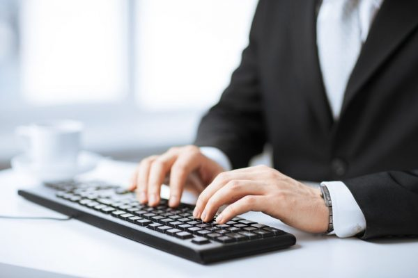 Picture Of Man Hands Typing On Keyboard to represent blogging as a source of online income without investment